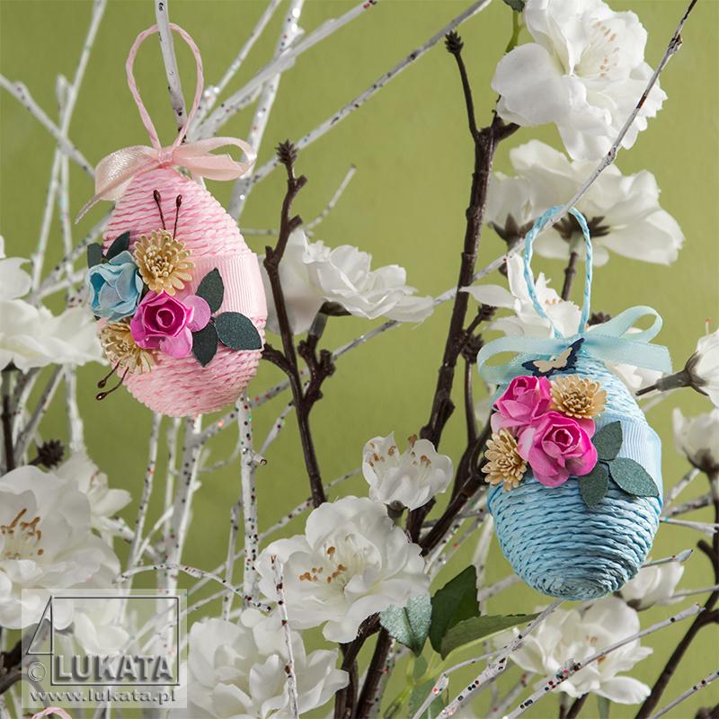 Różowe i niebieskie jajka wielkanocne na drzewku świątecznym.